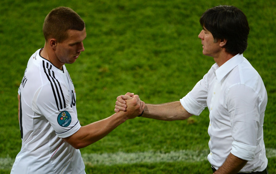 Lukas Podolski shakes hands with Joachim Low