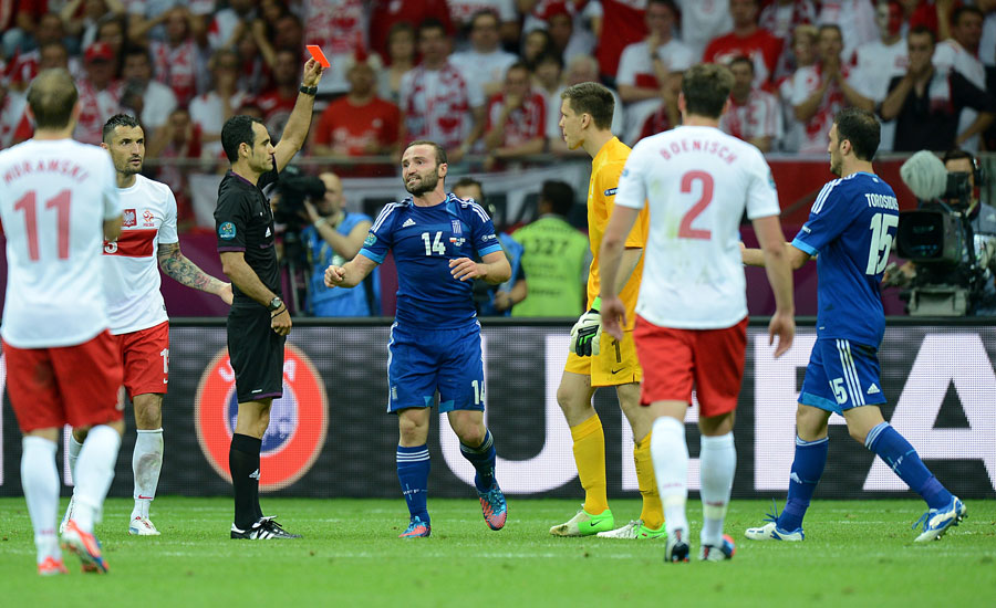 Referee Carlos Velasco Carballo (3rd left) shows Poland goalkeeper Wojciech Szczesny (3rd right) a straight red card