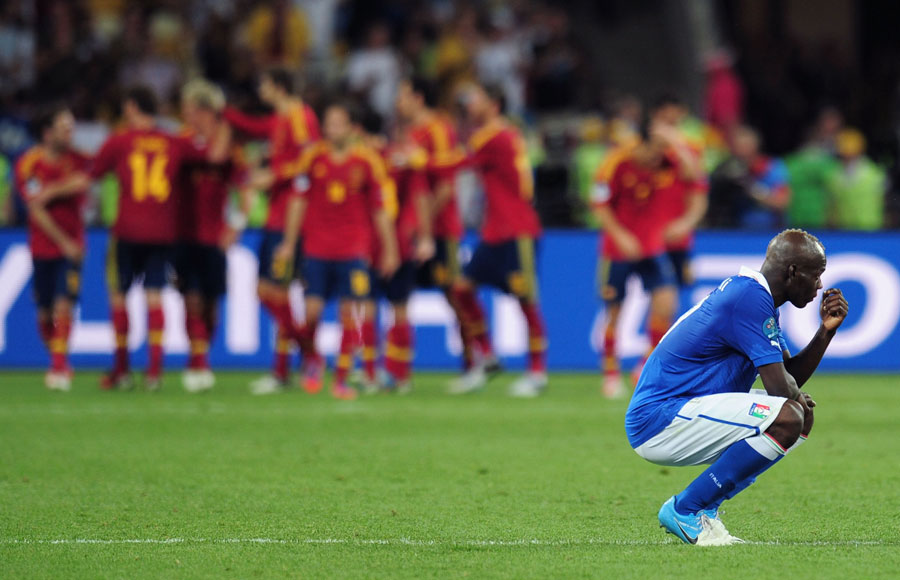 Mario Balotelli of Italy shows his dejection as the the Spanish team celebrate