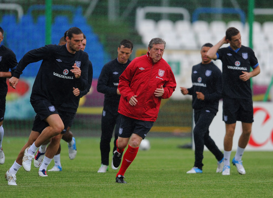 Andy Carroll trains alongside England manager Roy Hodgson