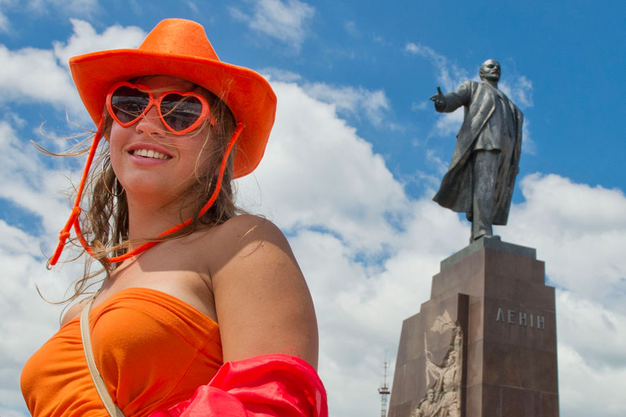 A Dutch soccer fan smiles as she walks by a statue of Lenin