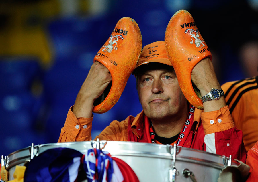 A Dutch fan sits dejected after watching his side crash out