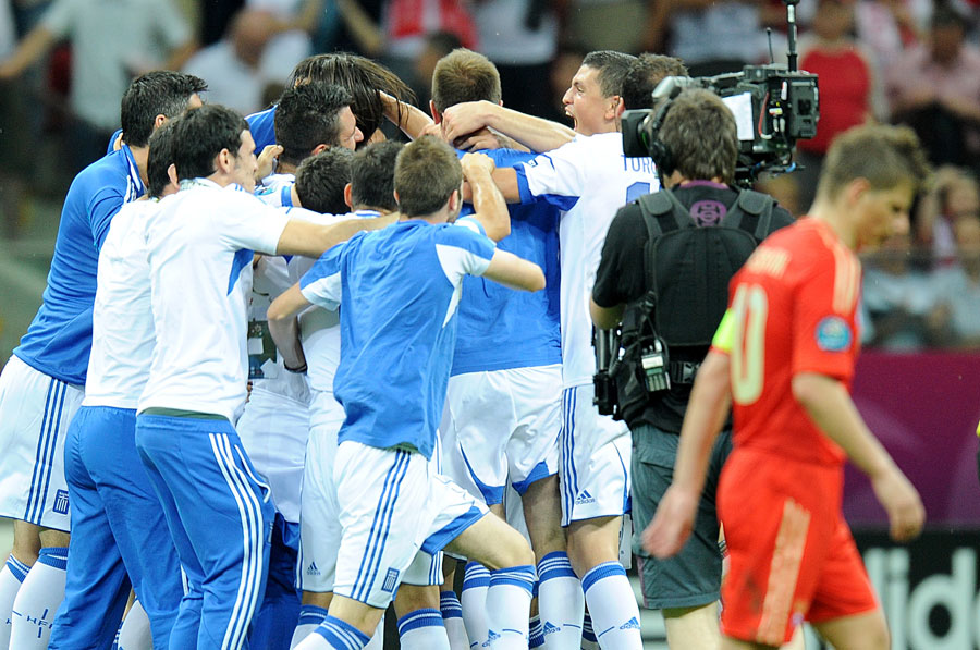 Russia's Andrey Arshavin leaves the field of play dejected after the final whistle, as Greece players and staff celebrate in the background