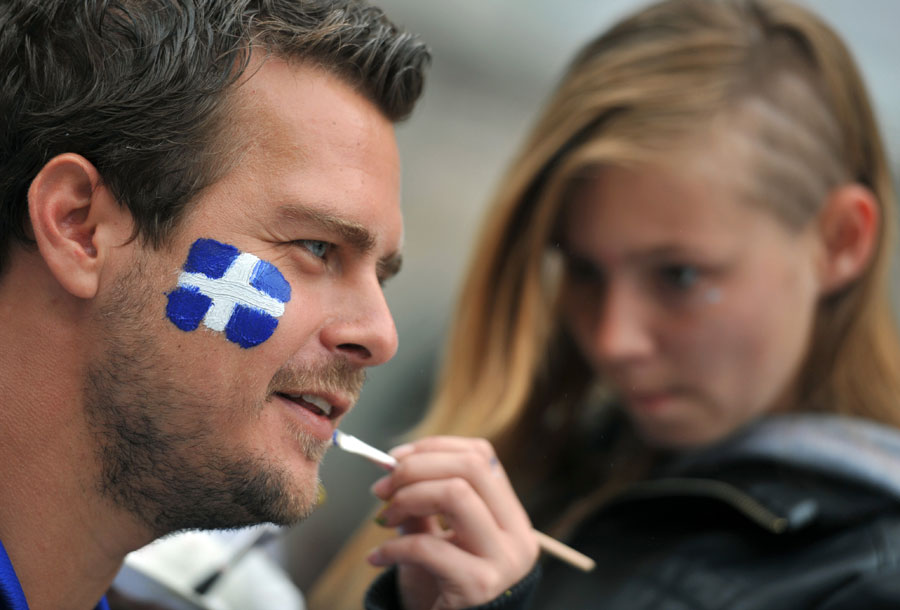 A supporter of Greece gets his face painted in the national colours prior to the game