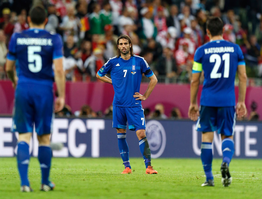 Greek players stand dejected as they went out