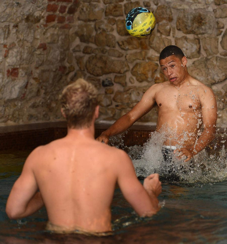 Alex Oxlade-Chamberlain heads a ball with Joe Hart