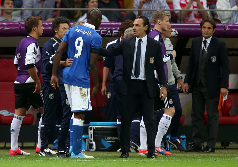 Italy's head coach Cesare Prandelli checks on the condition of Mario Balotelli after he picked up an injury