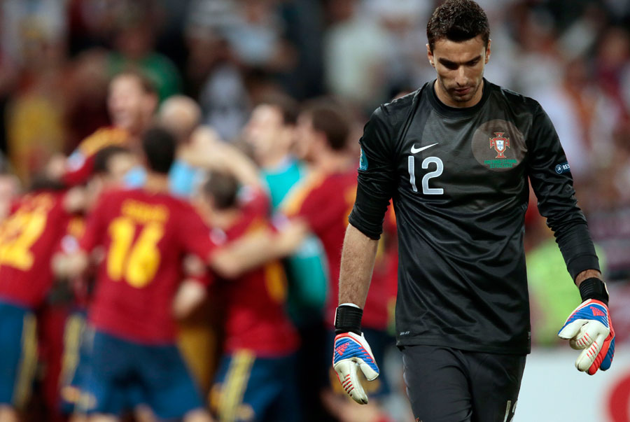 Portugal goalkeeper Rui Patricio walks past celebrating Spanish players following the defeat